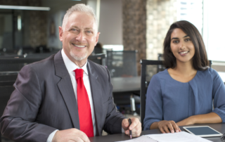 Older white male mentoring young indian female in finance